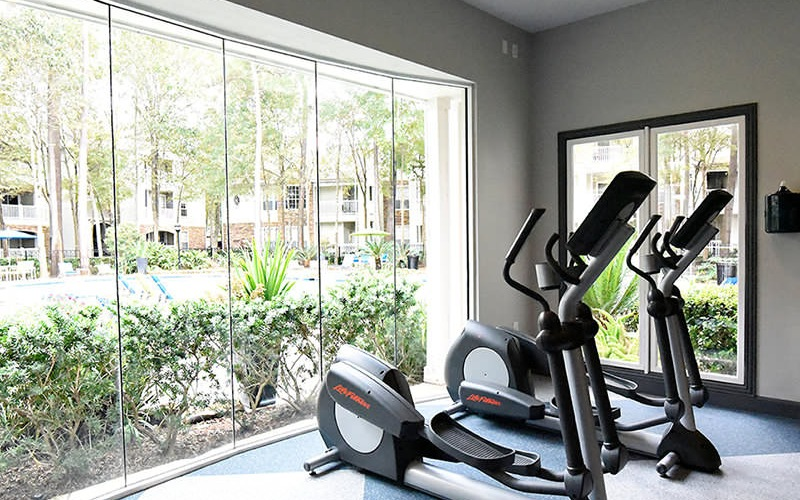 elliptical machines in fitness center in front of a wall of glass windows